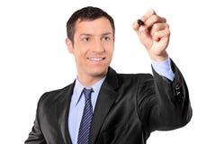 Hombre de negocios que sostiene una pluma negra Imagen de archivo