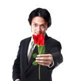 Hombre de negocios que sostiene una rosa, 40 años atractivos del hombre del asion encendido Imagen de archivo libre de regalías