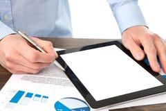Hombre de negocios que sostiene una tableta con la pantalla aislada en la tabla w fotografía de archivo