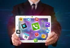 Hombre de negocios que sostiene una tableta con los apps y los iconos coloridos modernos Foto de archivo libre de regalías