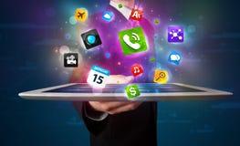 Hombre de negocios que sostiene una tableta con los apps y los iconos coloridos modernos Foto de archivo