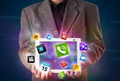 Hombre de negocios que sostiene una tableta con los apps y los iconos coloridos modernos Fotos de archivo libres de regalías
