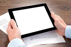 Hombre de negocios que sostiene una tableta en la tabla con los documentos imagenes de archivo