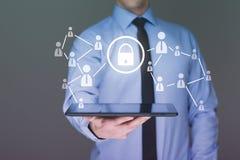 Hombre de negocios que sostiene una tablilla con el interfaz de la pantalla táctil y el concepto cibernético de la seguridad Imagen de archivo
