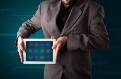 Hombre de negocios que sostiene una tablilla moderna blanca con los apps borrosos Fotografía de archivo
