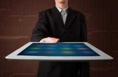 Hombre de negocios que sostiene una tablilla moderna blanca con los apps borrosos Fotografía de archivo libre de regalías