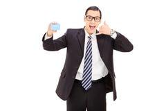 Hombre de negocios que sostiene una tarjeta azul en blanco Imagen de archivo