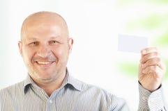 Hombre de negocios que sostiene una tarjeta de visita en blanco Fotografía de archivo