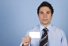 Hombre de negocios que sostiene una tarjeta en blanco Fotos de archivo