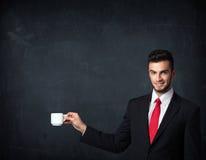 Hombre de negocios que sostiene una taza blanca Foto de archivo libre de regalías