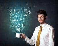 Hombre de negocios que sostiene una taza blanca con los iconos del negocio Imagenes de archivo