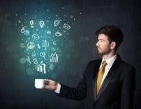 Hombre de negocios que sostiene una taza blanca con los iconos del negocio Foto de archivo