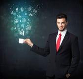 Hombre de negocios que sostiene una taza blanca con los iconos del negocio Foto de archivo libre de regalías