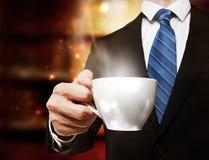Hombre de negocios que sostiene una taza de café Imagen de archivo libre de regalías