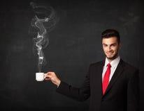 Hombre de negocios que sostiene una taza tórrida blanca Imagen de archivo libre de regalías
