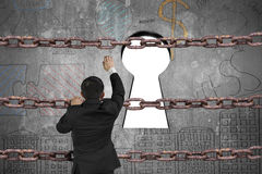 Hombre de negocios que sube en la cadena del hierro para el ojo de la cerradura con blanco en blanco Fotografía de archivo libre de regalías