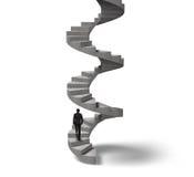 Hombre de negocios que sube la escalera espiral concreta Imagen de archivo libre de regalías
