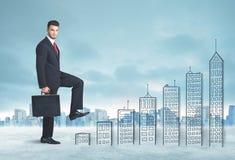 Hombre de negocios que sube para arriba a mano edificios dibujados en ciudad Foto de archivo