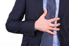 Hombre de negocios que sufre de ardor de estómago. Foto de archivo