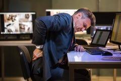 Hombre de negocios que sufre de dolor de espalda fotos de archivo