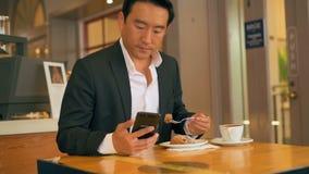 Hombre de negocios que tiene comida mientras que usa el teléfono móvil 4k almacen de metraje de vídeo