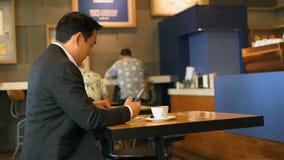 Hombre de negocios que tiene comida mientras que usa el teléfono móvil 4k metrajes