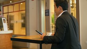 Hombre de negocios que tiene comida mientras que usa el teléfono móvil 4k almacen de video