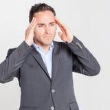 Hombre de negocios que tiene dolor de cabeza foto de archivo