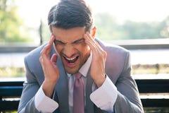 Hombre de negocios que tiene dolor de cabeza al aire libre Foto de archivo libre de regalías