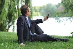 Hombre de negocios que tiene una rotura en el parque Foto de archivo libre de regalías