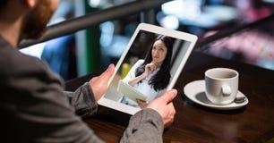 Hombre de negocios que tiene videoconferencia con la mujer en la tableta imagenes de archivo