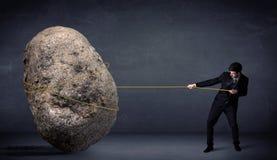 Hombre de negocios que tira de la roca enorme con una cuerda Imagen de archivo