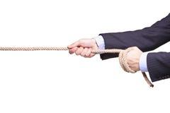 Hombre de negocios que tira de una cuerda Imagenes de archivo