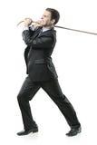 Hombre de negocios que tira de una cuerda Imagen de archivo