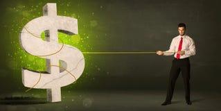 Hombre de negocios que tira de una muestra de dólar verde grande Foto de archivo