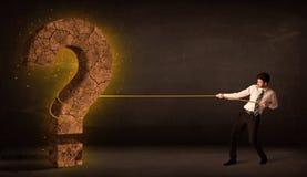 Hombre de negocios que tira de una piedra sólida grande del signo de interrogación Imagen de archivo libre de regalías