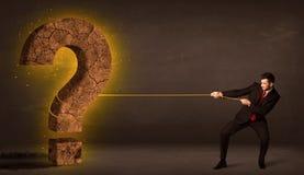 Hombre de negocios que tira de una piedra sólida grande del signo de interrogación Imagen de archivo