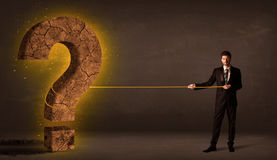 Hombre de negocios que tira de una piedra sólida grande del signo de interrogación Imagenes de archivo