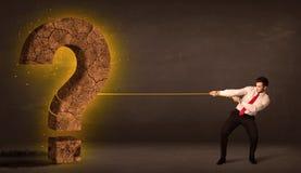 Hombre de negocios que tira de una piedra sólida grande del signo de interrogación Foto de archivo libre de regalías