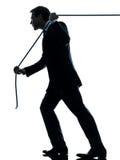 Hombre de negocios que tira de una silueta de la cuerda Foto de archivo libre de regalías