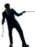 Hombre de negocios que tira de una silueta de la cuerda Fotografía de archivo libre de regalías