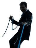 Hombre de negocios que tira de una silueta de la cuerda Imagen de archivo