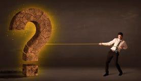 Hombre de negocios que tira de una piedra sólida grande del signo de interrogación Fotografía de archivo