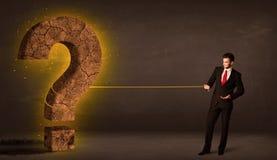 Hombre de negocios que tira de una piedra sólida grande del signo de interrogación Fotografía de archivo libre de regalías