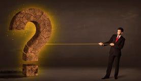 Hombre de negocios que tira de una piedra sólida grande del signo de interrogación Imágenes de archivo libres de regalías