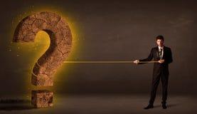 Hombre de negocios que tira de una piedra sólida grande del signo de interrogación Foto de archivo