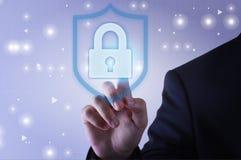 Hombre de negocios que toca el icono de la protección del escudo en la pantalla virtual imagenes de archivo