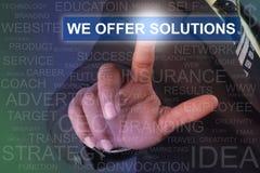 Hombre de negocios que toca OFRECEMOS el botón de las SOLUCIONES en la pantalla virtual imagen de archivo libre de regalías