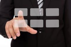 Hombre de negocios que toca una pantalla imaginaria contra Foto de archivo libre de regalías