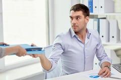 Hombre de negocios que toma la carpeta de la secretaria en oficina Imágenes de archivo libres de regalías